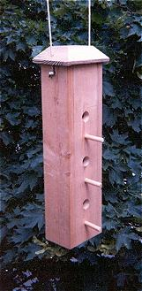 A song bird feeder suspended from a post in a yard with trees in the background.